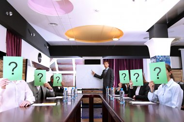Businessmen with question marks on their faces before business training