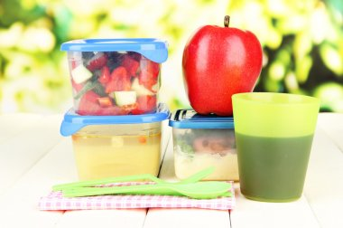 Tasty lunch in plastic containers, on wooden table on bright background