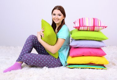 Beautiful young girl with pillows in room