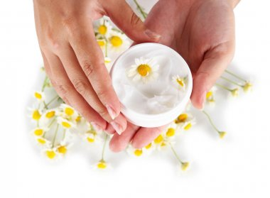 Cream with chamomile in hand isolated on white