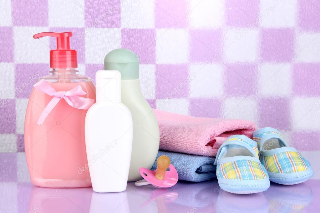 Bambino cosmetici e asciugamani in bagno viola sfondo muro di