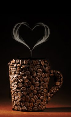 Cup of coffee beans with smoke in shape of heart on brown background