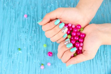 Beautiful woman hands with blue manicure holding pink beads, on color background