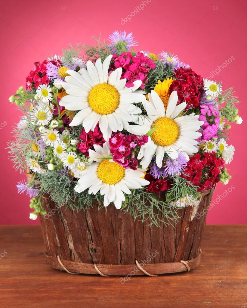 Beautiful Bright Flowers In Wooden Basket On Table On Pink