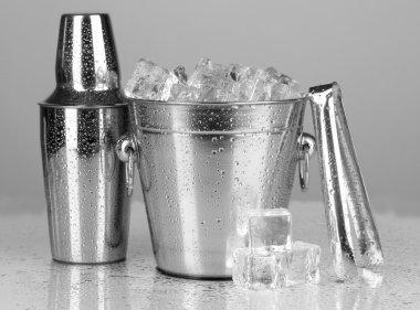 Metal ice bucket and shaker on grey background