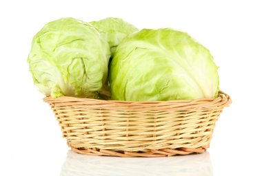 Green cabbage in wicker basket, isolated on white