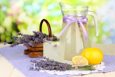 Lavender lemonade in glass jug and cocktail glasses, on bright background