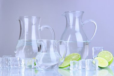 Glass pitchers of water with ice and lime on grey background