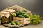 Photo fresh cucumbers in wooden box, pickles and dill, on grey background