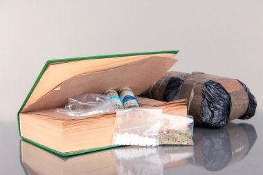 Narcotics in book-hiding place and packages on gray background