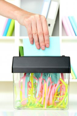 Hand putting paper into shredder machine, on office interior background