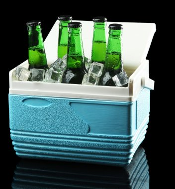 Bottles of beer with ice cubes in mini refrigerator, on black background