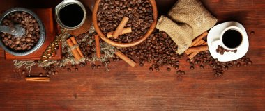 Coffee beans, metal turk and coffee mill on wooden background with copy space