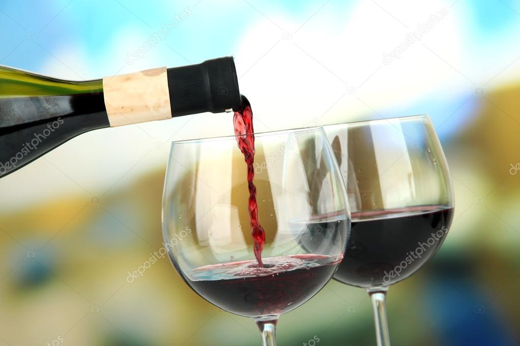 Lichte Rode Wijn : Rode wijn wordt gegoten in een glas wijn op lichte achtergrond