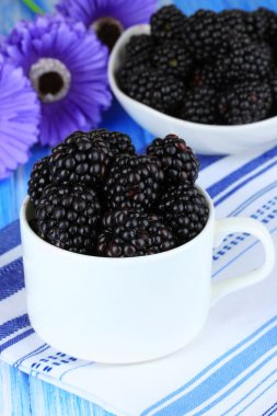 Sweet blackberries in cup on table close-up