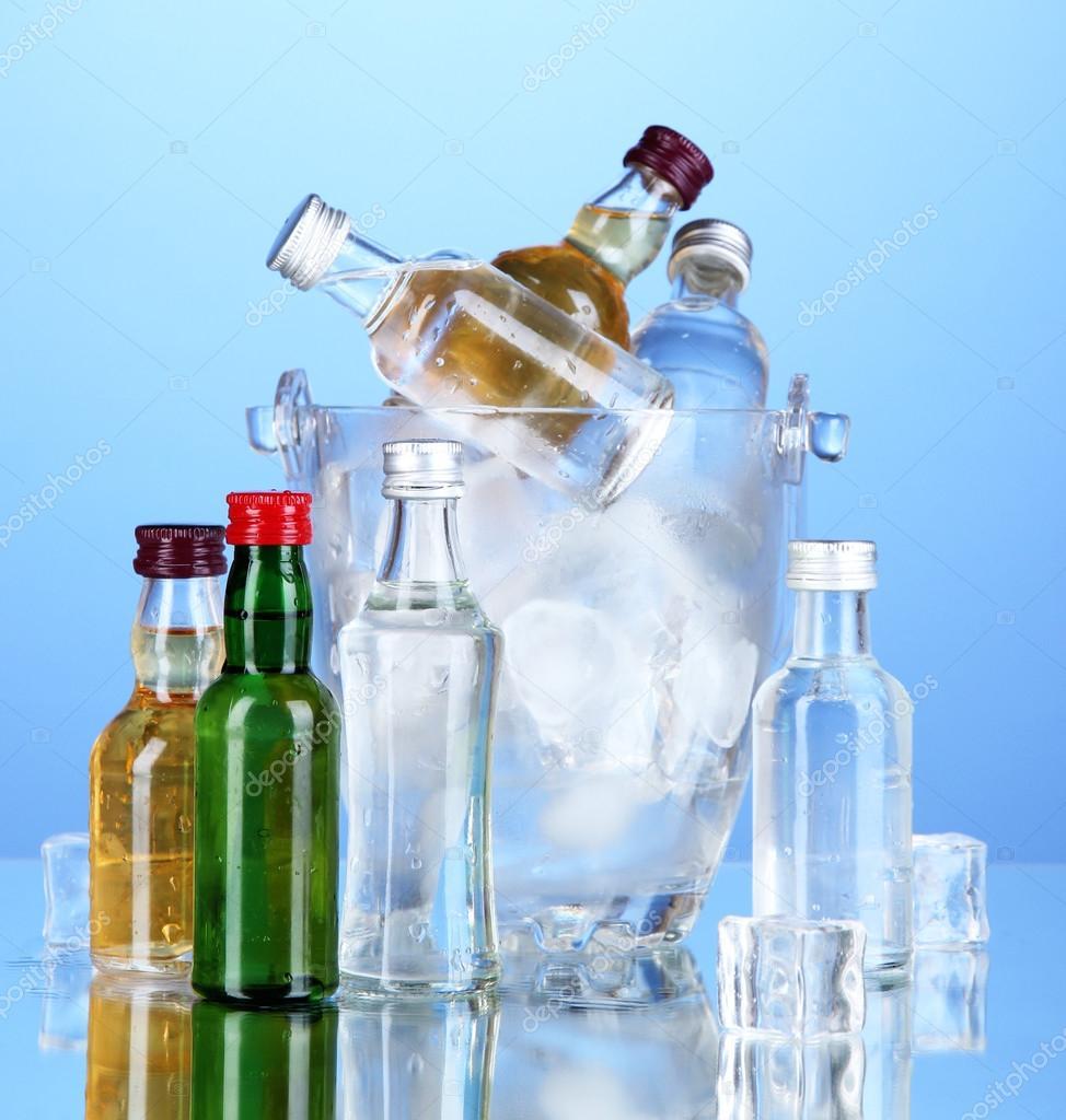 Minibar-Flaschen in Eimer mit Eiswürfeln auf farbigem Hintergrund ...