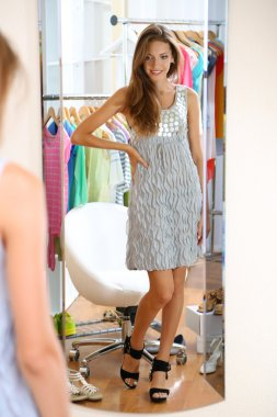 Beautiful girl trying shoes near mirror on room background