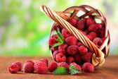 Photo Ripe sweet raspberries in basket on wooden table, on green background