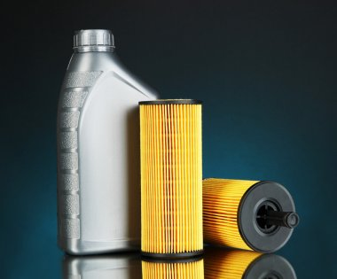 Car oil filters and motor oil can on dark color background