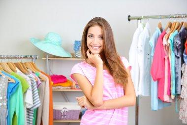 Beautiful young woman in walk-in closet