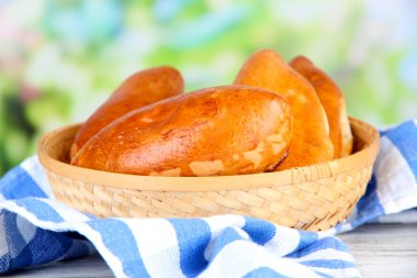 Fresh baked pasties, in wooden bowl, on wooden table, on bright background
