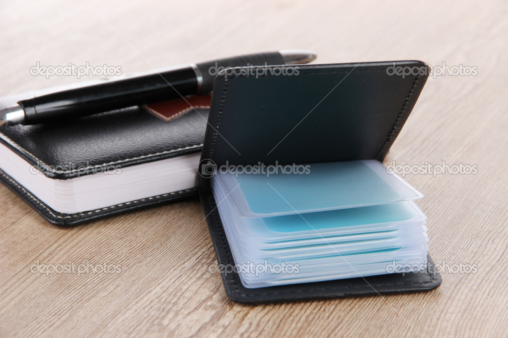 Black business card holder notebook and pen on wooden background ...