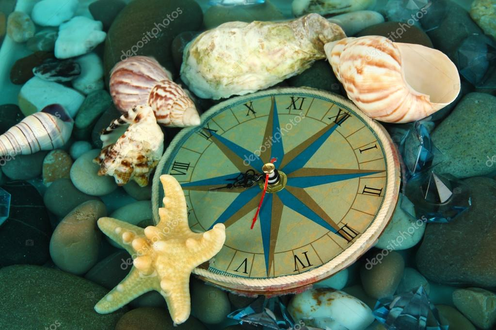 Clock on sea bottom with shells and stones
