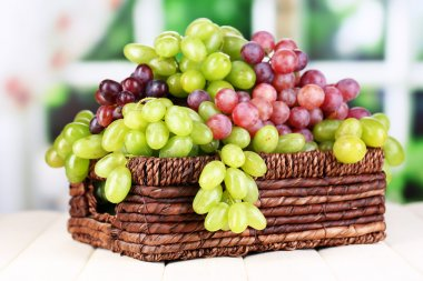 Ripe green and purple grapes in basket on wooden table on natural background