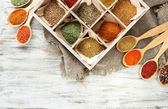 Assortment of spices in wooden spoons and box, on wooden background