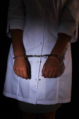 Doctor in handcuffs on dark background
