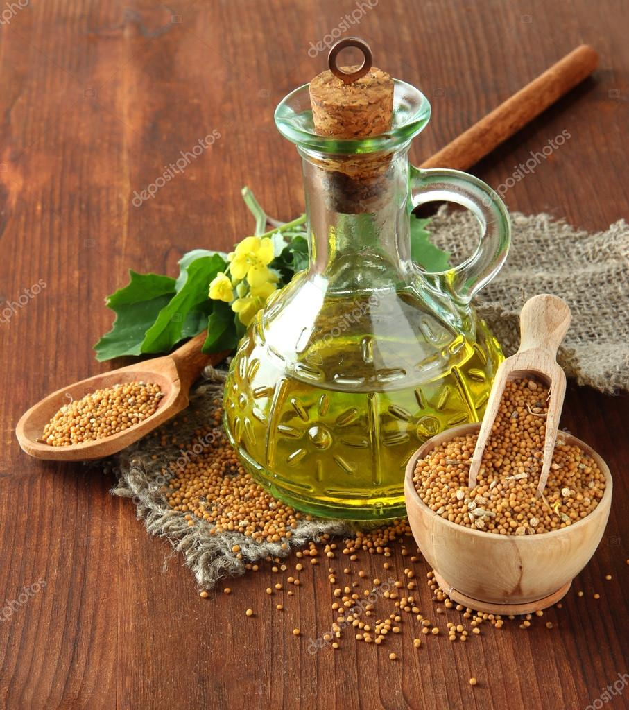 Jar of mustard oil and seeds with mustard flower on wooden