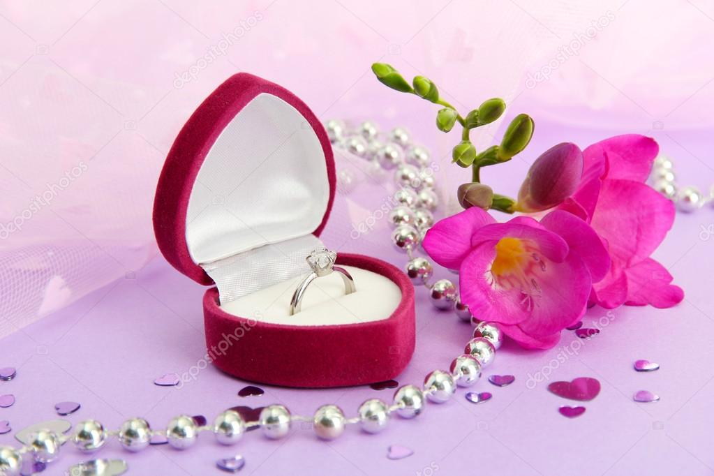 beautiful box with wedding ring and flower on purple