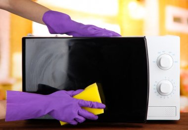 Hand with sponge cleaning microwave oven, on bright background