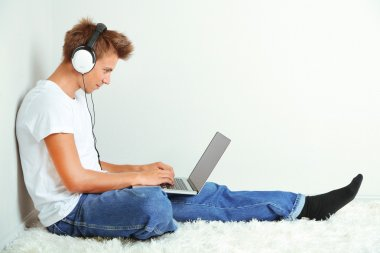 Young man relaxing on carpet and listening to music, on gray wall background
