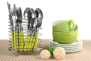 Kitchen cutlery in metal stand with clean dishes on tablecloth on white background