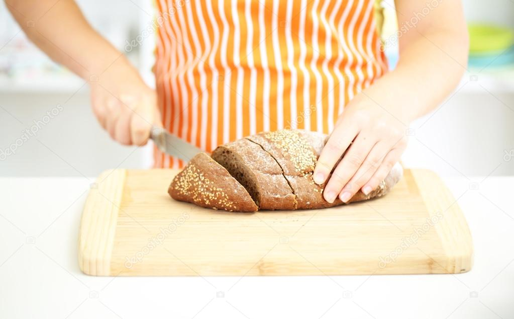 Woman slicing bread with sesame seeds on chopping board, close up