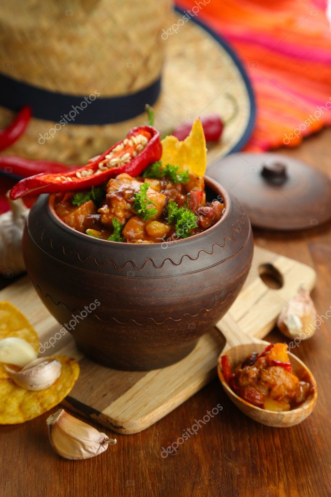 Chili Corn Carne - traditional mexican food, in pot, on napkin, on wooden background
