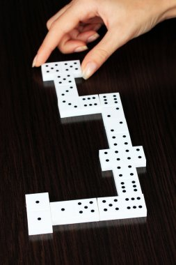 Hand playing domino on wooden background