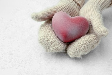Female hands in mittens with red heart, close-up