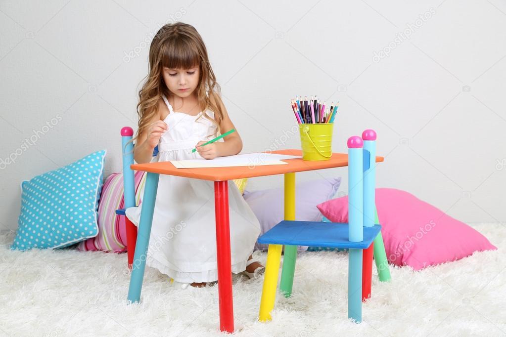 Klein meisje trekt vergadering aan tafel in kamer op grijs muur