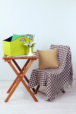 Magazines and folders in green box on table in room