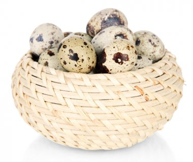 Quail eggs in wicker basket isolated on white