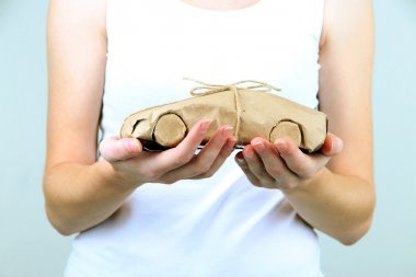 Woman hands holding a car wrapped in brown kraft paper