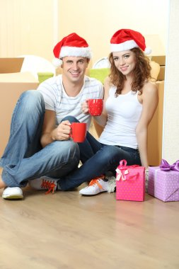 Young couple with boxes in new home celebrating New Years