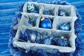 vánoční hračky v dřevěné krabici na modrém pozadí