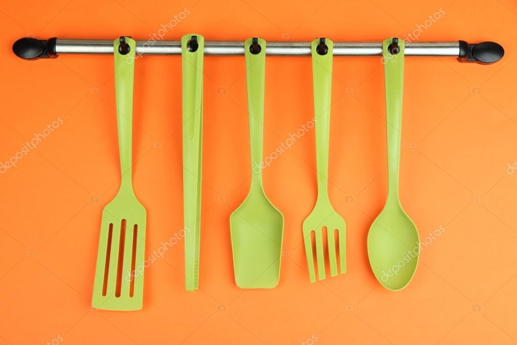 Plastic Kitchen Utensils On Silver Hooks On Orange Background U2014 Stock Photo