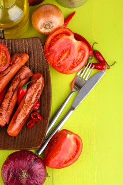 Delicious sausages with vegetables on plate on wooden table close-up