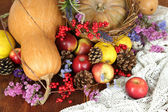 Autumn composition of fruits, pumpkins and flowers on table close-up