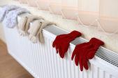 Fotografie gestrickte Handschuhe trocknen am Heizkörper