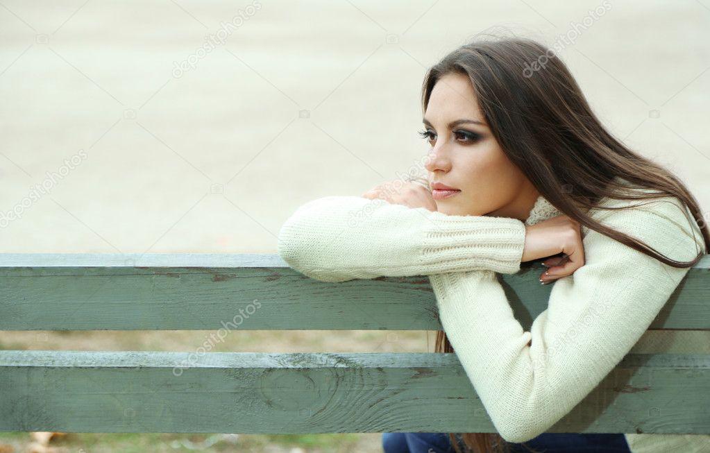 Фотообои Молодая одинокая женщина на скамейке в парке